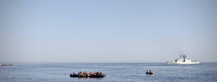 Kriegsschiff mit Migrantenboot