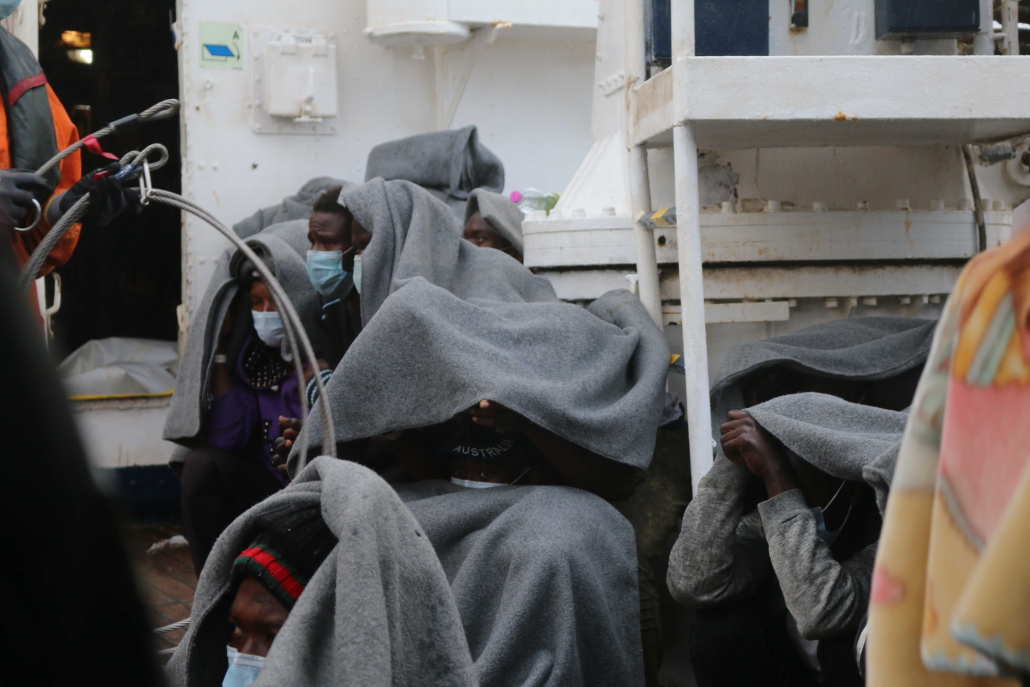Freezing rescued persons with blankets in the rain